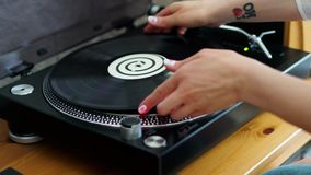 Woman turns on the turntable and puts the LP. To listen to the music stock video footage