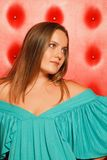 Woman in a turquoise dress, near to red wall stock images