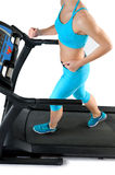 Woman in turquoise sportswear and sneakers runs on a treadmill. Stock Image