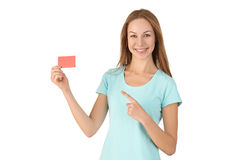 Woman in turquoise t-shirt points finger at the card. Stock Photo