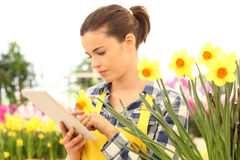 Woman tusing tablet computer in flowers garden Stock Photography