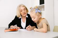 Woman tutor with girl in the classroom. stock images