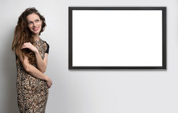 Woman and TV hanging on the wall Royalty Free Stock Photography