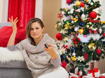 Woman with TV remote control near Christmas tree Stock Image