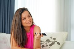 Young woman watching tv on sofa. Woman with tv remote control on sofa Stock Images