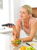 Woman with the TV remote while preparing dinner Stock Photo