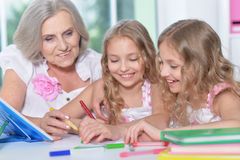 Woman with tweenie   girls doing homework Stock Photo