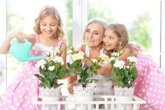Woman with tweenie   girls watering flowers Stock Images