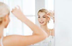 Woman with tweezers tweezing eyebrow at bathroom Stock Photography
