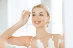 Woman with tweezers tweezing eyebrow at bathroom Royalty Free Stock Photos