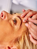 Woman tweezing eyebrow by beautician Royalty Free Stock Images