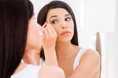 Woman tweezing eyebrows. Beautiful young woman tweezing eyebrows while looking at the mirror Stock Photography