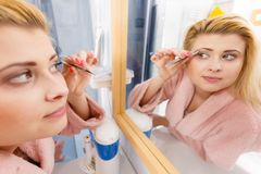 Woman tweezing eyebrows depilating with tweezers. Woman in bathroom plucking eyebrows depilating with tweezers, looking at mirror. Girl tweezing removing her royalty free stock photography