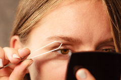 Woman tweezing eyebrows depilating with tweezers Royalty Free Stock Images