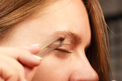 Woman tweezing eyebrows depilating with tweezers. Woman plucking eyebrows depilating with tweezers closeup part of face. Girl tweezing eyebrows royalty free stock image