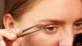 Woman tweezing eyebrows depilating with tweezers Stock Photo