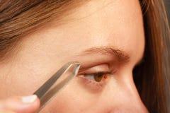 Woman tweezing eyebrows depilating with tweezers Stock Photos