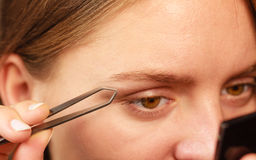 Woman tweezing eyebrows depilating with tweezers. Woman plucking eyebrows depilating with tweezers closeup part of face. Girl tweezing eyebrows royalty free stock photography