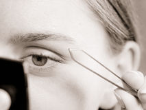 Woman tweezing eyebrows depilating with tweezers. Woman plucking eyebrows depilating with tweezers closeup part of face. Girl tweezing eyebrows, black & white stock images