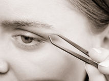 Woman tweezing eyebrows depilating with tweezers Royalty Free Stock Image