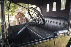 Woman in Twenties Attire Near Antique Automobile Stock Photo
