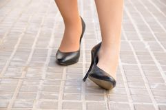 Woman with ankle twisted. Woman with twisted ankle. Female foot in pain due to sprained ankle wearing stilettos on the city sidewalk Royalty Free Stock Photography