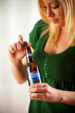Woman Twists Cap Off Of Bottle Of Bud Light. Bud Light Is Produc Royalty Free Stock Photos