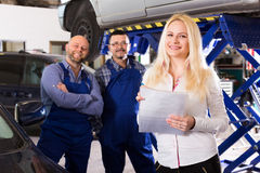 Woman and two auto mechanics Stock Photos