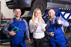 Woman and two auto mechanics Stock Images