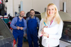 Woman and two auto mechanics Royalty Free Stock Photo