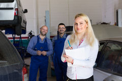 Woman and two auto mechanics Royalty Free Stock Photography