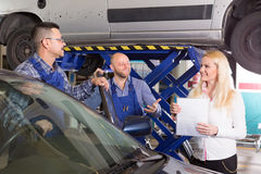 Woman and two auto mechanics. Attractive young female insurance agent discussing with smiling auto mechanics renewal of car Royalty Free Stock Images