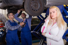 Woman and two auto mechanics Stock Photography