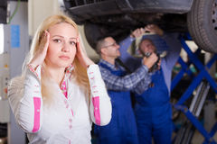 Woman and two auto mechanics Royalty Free Stock Images