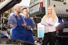 Woman and two auto mechanics. Unpleased young blonde women talking with mechanics at auto service center. Selective focus Stock Photos