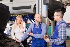 Woman and two auto mechanics Stock Photo