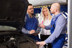 Woman and two auto mechanics Stock Photo