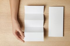Woman with two blank brochures on wooden background, top view. Mockup for design royalty free stock photos