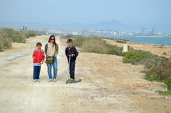 Woman And Two Boys With A Scooter. A women with two boys out for a walk along the beach royalty free stock photos