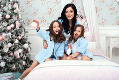 Woman with two children in  blue knit cardigan in the bed near Christmas tree. Young women with two girls of three and five years on the bed in the bedroom near Stock Photography