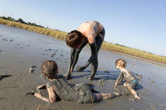 Woman with two children in healing mud Stock Images