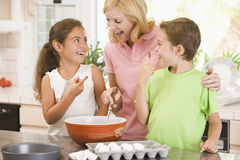 Woman and two children in kitchen baking Royalty Free Stock Images