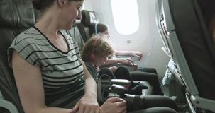 Woman and two children sit on a plane on a bumpy taxi across the tarmac. Woman and two children sit on a plane on a bumpy ride as the plane taxis across the stock video footage