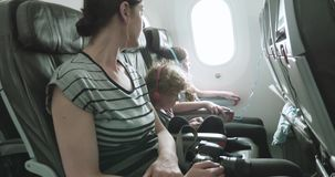 Woman and two children sit on a plane on a bumpy taxi across the tarmac. Woman and two children sit on a plane on a bumpy ride as the plane taxis across the stock video