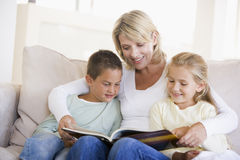 Woman and two children sitting in living room Stock Photos