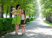 Woman and two children walking down the avenue Royalty Free Stock Photography