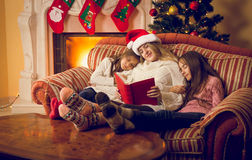 Woman and two daughters fell asleep at fireplace at Christmas ev Stock Photo
