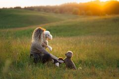 Woman and two dogs on a field at sunset. Walking with pet. Toy and small poodle