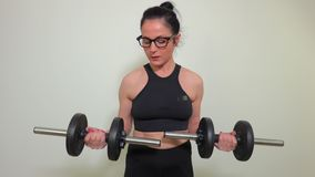Woman with two dumbbells doing exercises for biceps. In room stock video