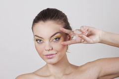Woman with two fingers near her face Stock Image